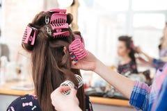Coiffeur de femme enlevant des bigoudis de longs cheveux de femelle photo libre de droits
