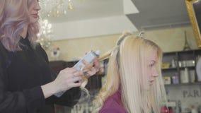 Coiffeur de femme faisant des boucles aux cheveux blonds avec des fers de bordage au salon de beauté banque de vidéos