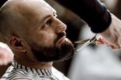 Coiffeur de mode habillé dans une barbe noire de ciseaux de vêtements d'homme brutal dans le raseur-coiffeur élégant photographie stock