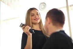 Coiffeur de sourire Using Electric Razor au client photos libres de droits