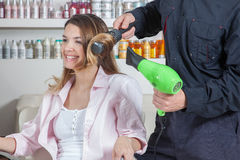 The coiffeur drys  the hair one woman Royalty Free Stock Photo