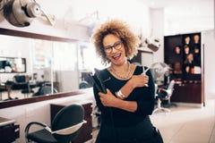 Coiffeur féminin au salon tenant des outils de coiffure Images stock