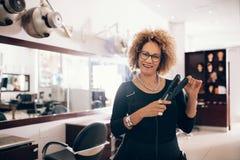 Coiffeur féminin au salon tenant un redresseur de cheveux Photo libre de droits