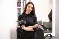 Coiffeur féminin professionnel avec le dessiccateur et les ciseaux photos stock