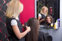 Coiffeur féminin redressant les cheveux de la femme dans le salon de beauté Image libre de droits