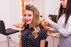 Coiffeur féminin tenant et faisant la coiffure à la belle jeune femme mignonne photo libre de droits