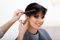 Coiffeur faisant la coiffure Brune avec les cheveux courts dans le salon Images libres de droits