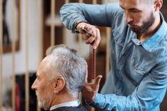 Coiffeur faisant la coupe de cheveux à l'homme supérieur Images stock