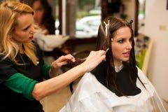 Coiffeur faisant le traitement de cheveux à un client dans le salon Image libre de droits