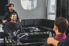 Coiffeur habile préparant le client pour la coupe de cheveux photo stock