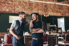 Coiffeur heureux avec le client se tenant au raseur-coiffeur Photographie stock