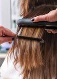 Coiffeur à l'aide d'un redresseur de cheveux Images libres de droits