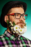 Coiffeur man. Funny young man with a beard of flowers wearing elegant bowler hat and glasses royalty free stock photos