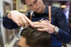 Coiffeur masculin coupant des cheveux au raseur-coiffeur photographie stock libre de droits