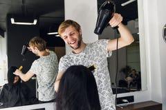Coiffeur masculin souriant et parlant avec un client tout en faisant une nouvelle coupe de cheveux à la belle jeune femme de brun photos stock