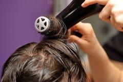 Coiffeur modelant des cheveux par le dessiccateur et le peigne photo stock