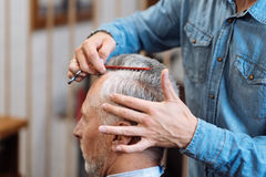 Coiffeur peignant des cheveux de vieil homme Image libre de droits