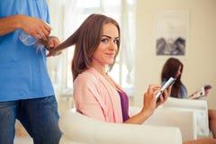 Coiffeur peignant la femme de cheveux avec le téléphone portable dans la coiffure photo stock