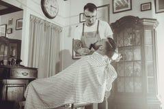 Coiffeur pendant le travail dans son salon de coiffure Image libre de droits