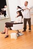 Coiffeur professionnel avec le sèche-cheveux Photographie stock