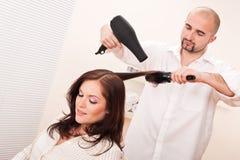 Coiffeur professionnel avec le sèche-cheveux images stock