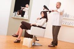 Coiffeur professionnel avec le sèche-cheveux au salon Photo stock