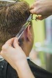 Coiffeur professionnel dénommant des cheveux de son client photographie stock