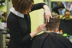 Coiffeur professionnel dénommant des cheveux de son client images libres de droits