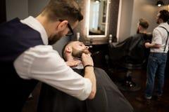 Coiffeur rasant le jeune homme avec le rasoir images stock