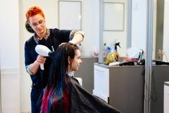 Coiffeur séchant les cheveux femelles de client avec le dessiccateur de main dans le salon de coiffure photo libre de droits