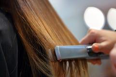 Coiffeur s'chargeant de la coiffure par le redresseur photographie stock