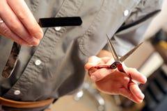 Coiffeur tenant des ciseaux et des mains de rasoir dans le raseur-coiffeur Photographie stock