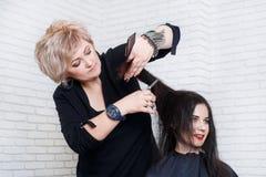 Coiffeur travaillant avec des cheveux du ` s de client Photographie stock libre de droits