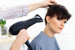 Coiffeur Using Dryer sur les cheveux humides de femme dans le salon.  Cheveux courts. Image libre de droits
