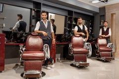 Coiffeurs sûrs de maîtres tenant les chaises proches et la pose de coiffeur images libres de droits