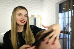 Coiffeuse Making Haircut de jeune femme avec le peigne photo stock
