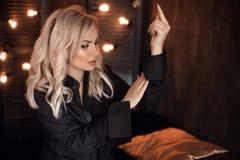 coiffure Beau portrait blond de femme posant dans la chemise noire Modèle blond à la mode de fille au-dessus de fond foncé de lum image libre de droits