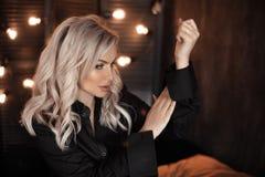 coiffure Beau portrait blond de femme posant dans la chemise noire Modèle blond à la mode de fille au-dessus de fond foncé de lum photos libres de droits