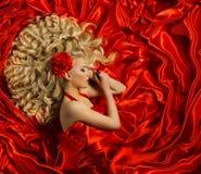 Coiffure, coiffure bouclée de femme, mannequin sur la couleur rouge Photographie stock