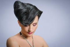 Coiffure quiff. Portrait of beautiful girl with elegant coiffure quiff in black dress Royalty Free Stock Image