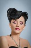 Coiffure quiff. Portrait of beautiful girl with elegant coiffure quiff in black dress Stock Photography