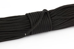 Coil of dark rope paracord on a white background Royalty Free Stock Image