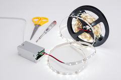 Coil luminous LED strip light and voltage transformer. Royalty Free Stock Photography