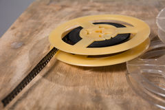 Coil with 8 mm of film lies on a wooden surface Royalty Free Stock Images