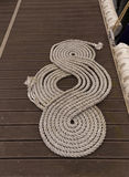 Coil of mooring nautical rope (hemp) folded in helix shape on pier Stock Image