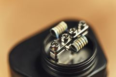 Coil of RDA atomizer for vaping or e-cigarette, vape macro footage. Toned Stock Photos