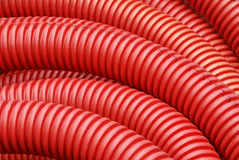Coil of red plastic corrugated plumbing pipe. In close up. Can be used as background Stock Photos