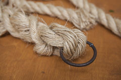 Coil of rope with a marine unit, and an iron ring. Stock Photos