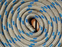 Coil of rope texture photo. Rope coiled up in spiral on board boat with blue and white circular texture pattern Stock Photo