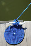 Coil of rope by water. Elevated view of blue coil of rope on quayside or pier by water Royalty Free Stock Photo
